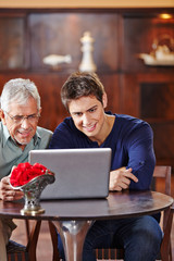 Senior und Mann schauen auf Laptop