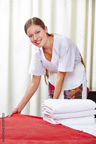 Zimmermädchen macht Bett in Hotelzimmer