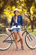 young woman posing next to bike
