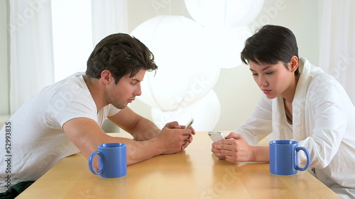Man and woman distracted by their smartphones