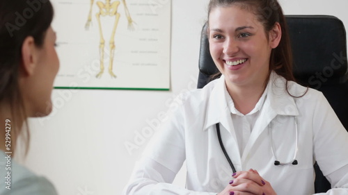Young smiling doctor talking to her female patient at office