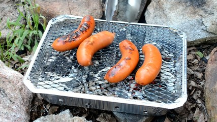 sausages cooking on a disposable barbecue outdoors
