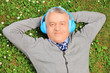 Mature man lying on grass with headphones, listening to music