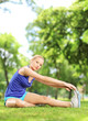 Young blond woman exercising outdoors in park
