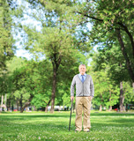 Full length portrait of a senior man walking with a cane in a pa