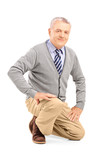 Smiling mature man kneeling