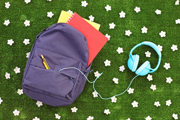 School backpack with books and headphones on a grass with daisy