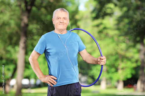 Mature athlete with headphones holding a hulahoop in park