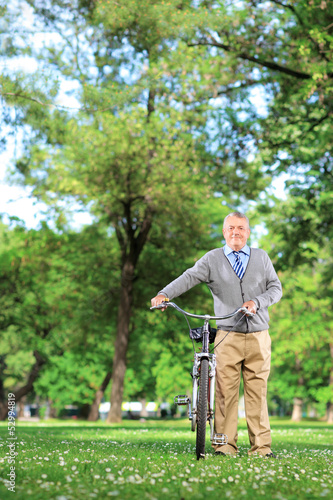 Mature man pushing a bicycle