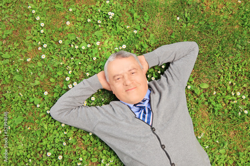 Senior man smiling and resting on grass in a park