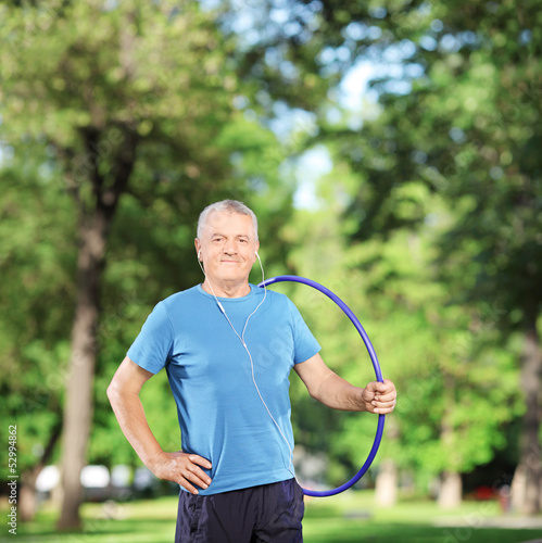 Smiling mature athlete with headphones holding a hulahoop in a p