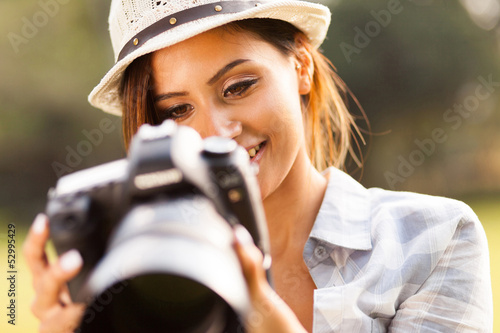 pretty woman reviewing photos on camera