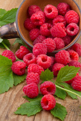 fresh raspberries with leafs  in a bowl on wooden table
