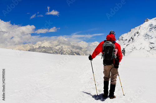 Mountain trekker looking at high winter Himalayas mountains