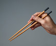 Male hand with  chopsticks.