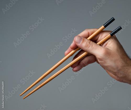 Male hand with  chopsticks.