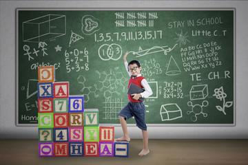 Asian boy step on crossword in class