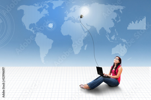 Asian female using laptop on world map