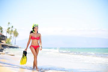 Beach woman walking by ocean - bikini and snorkel