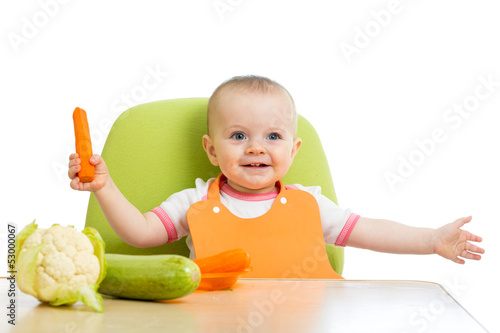 happy baby girl eating vegetables