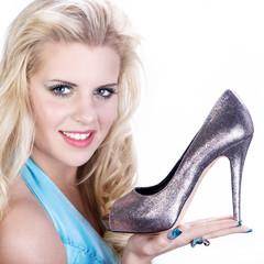 Hübsche junge Frau zeigt modischen Schuh