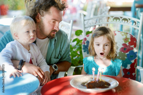 Little girl blowing out candles in her birthday