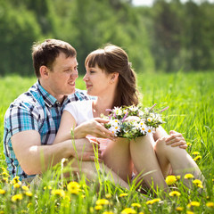 A young couple in a field of dandelions