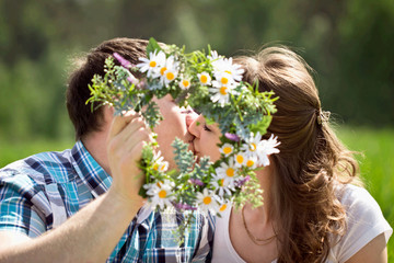 Loving couple kissing among the flowers