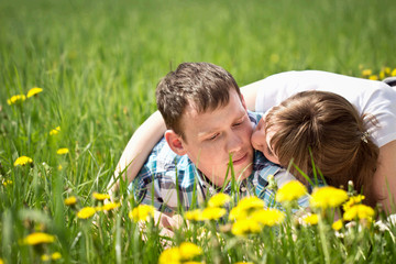 Young beautiful couple lying in a field of dandelions