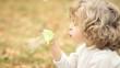 Happy child blowing soap bubbles in autumn park. Slow motion