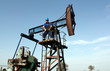 strong oil worker standing on pump jack