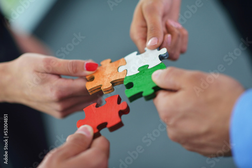 Leinwanddruck Bild Group of business people assembling jigsaw puzzle