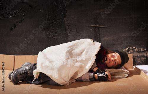 Beggar boy sleeping on cardboard sheet