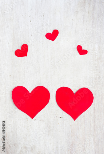 Big and small hearts on the white wood board