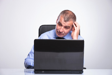 old business man looks puzzled at laptop
