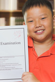 Young asian boy with full score examination sheets poster