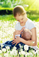 mother feeding her baby in nature green meadow with white flower