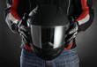 Leinwanddruck Bild - Motorcyclist with helmet in his hands. Dark background