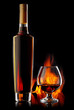 Bottle and glass of cognac over dark background with flame