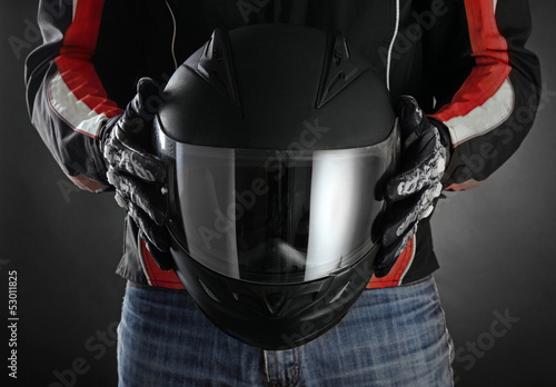 Leinwanddruck Bild Motorcyclist with helmet in his hands. Dark background