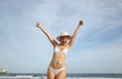 young woman at the beach with thumbs up