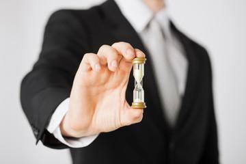 man hand holding hourglass