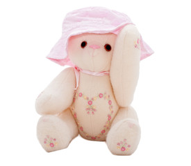 Summer teddy bear putting on a pink hat