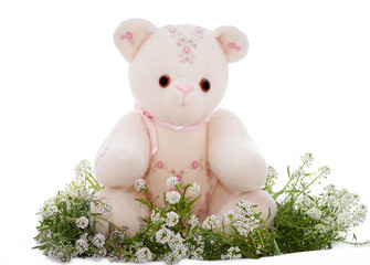 Spring teddy bear sitting on a bed of flowers