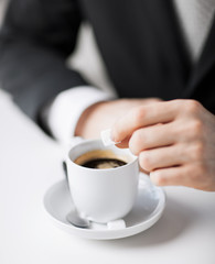 man putting sugar into coffee