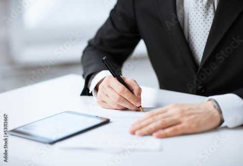 man with tablet pc signing paper