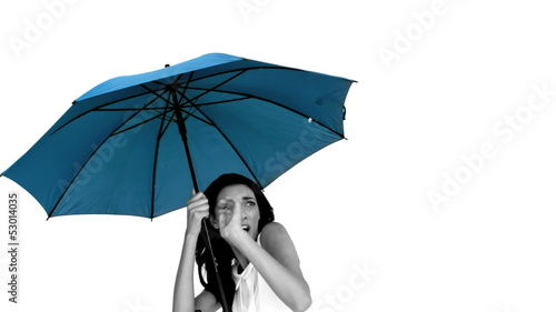 Woman under blue umbrella cowering with fear