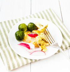 Breakfast with fried cutted egg, brussels sprouts and radish on