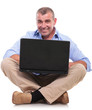 casual old man sits and works at laptop