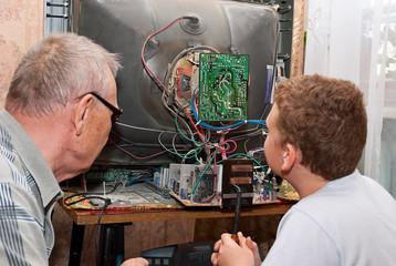 Дедушка и внук чинят старый телевизор